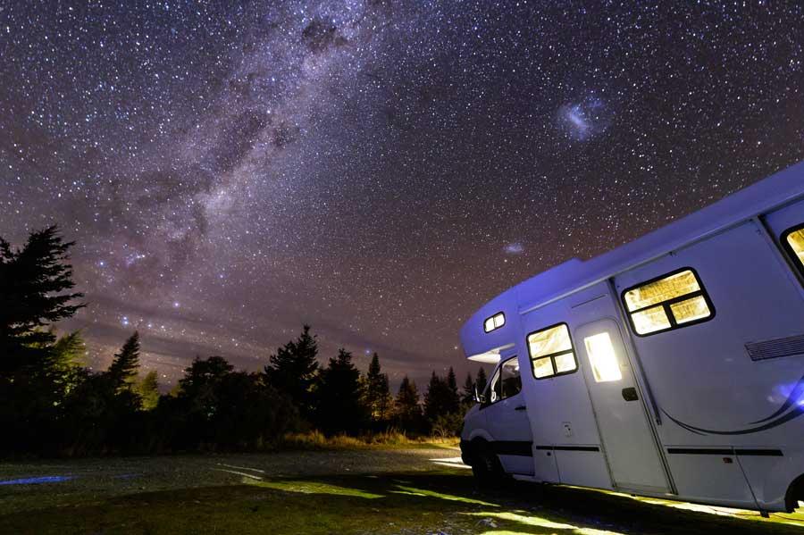 Motorhome parked in field underneath stars